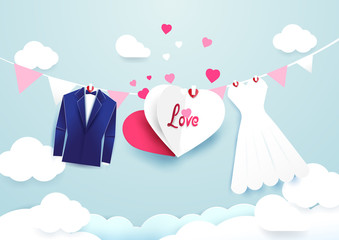White dress and blue suit with heart sign hanging on cloud sky background