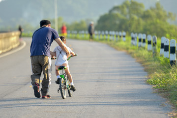 Little kid boy of 3 years and his father in autumn forest with a bicycle. Dad teaching his son. Man happy about success. Child with helmet. Safety sports