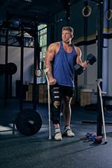Bodybuilder on crutches holds dumbbell.