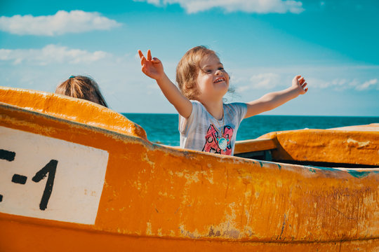 Two little girls play in a yellow old fishing boat on the beach in summer