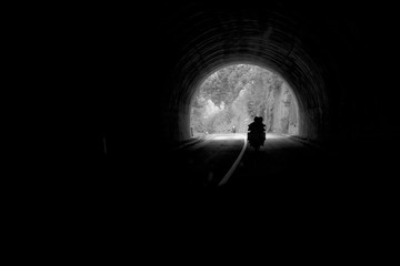 Silhouette of motorbikes in tunnel - black and white
