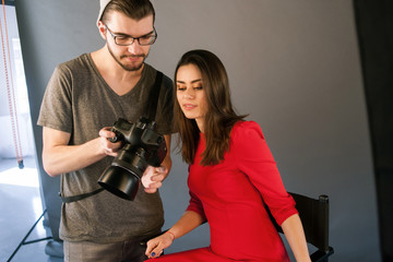 Photographer communicate with model on photoshoot. Man with camera show pictures to woman in red dress during the studio session. Production of commercials backstage