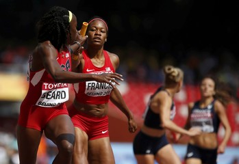 Phyllis Francis of the U.S. (2nd L) passes the baton to her teammate Jessica Beard in the women's 4 x 400 metres relay heat during the 15th IAAF World Championships at the National Stadium in Beijing