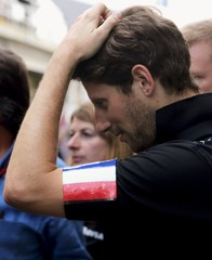 Grosjean of France wears a French national flag on his left arm before talking to the media after the qualifying session for the Brazilian F1 Grand Prix in Sao Paulo