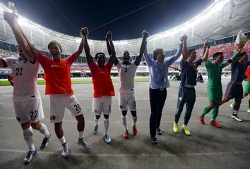 Hong Kong players and coach Kim Pang-on acknowledge supporters after drawing against China in their 2018 World Cup qualifying soccer match in Shenzhen