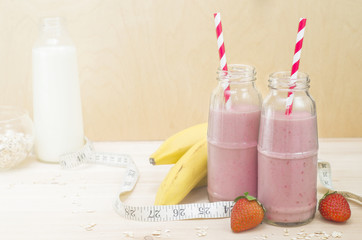 Milkshake in a glass bottle. Useful smoothies with banana, strawberries and oat, healthy breakfast. Picture with space for text or logo