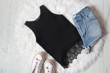 Black top with lace, denim shorts and sneakers on white fur, wooden background. Fashionable concept