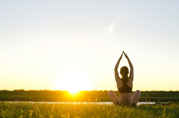Young woman meditating in lotus position on the river bank, sunset.