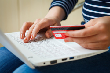 Girl's hand holding plastic credit card. A woman buys on the Internet. The return of cashback. Online shopping.