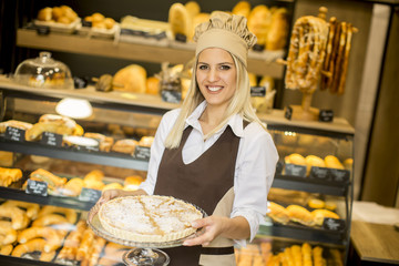 Bakery female worker posing with apple tart in baker shop