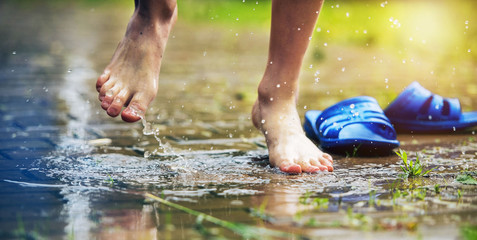 Bare feet of a child jumping into a puddle of rain
