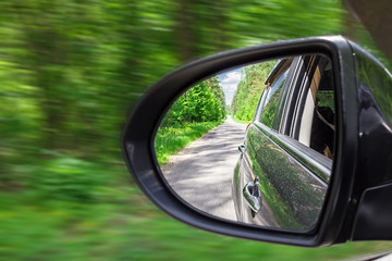 A view in the side view mirror. Mirror rear car. Reflection of the road