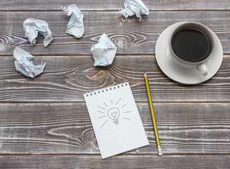 Ideal idea concept with crumpled paper and a lightbulb painted on a notebook. A cup of coffee, a gold pencil. On a wooden table. business idea.