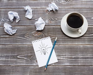 Ideal idea concept with crumpled paper and a lightbulb painted on a notebook. A cup of coffee, a pencil. On a wooden table. business idea.