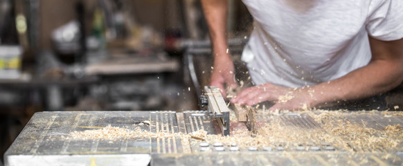 a man working with wood product on the machine