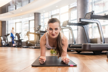 Front view of a young fit woman smiling while practicing the forearm plank exercise for core strength indoors at the gym