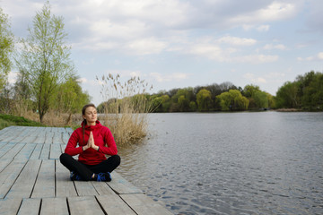 Woman meditating sitting in lotus, on near river, nature, park, natural background