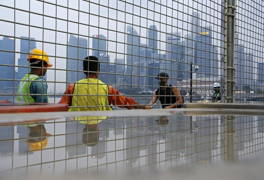 Workers pick up litter outside the fences of the Marina Bay circuit as a man wearing a mask passes ahead of the Singapore F1 night race in Singapore