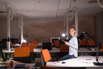 woman working on digital tablet in night office