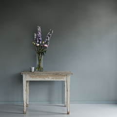 an old wooden table with coffee cup and flower bouquet