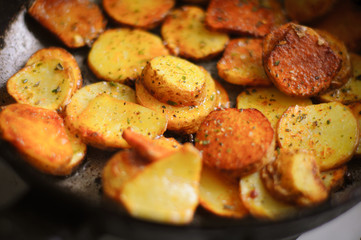 Fried potatoes in a frying pan sprinkled with seasoning
