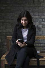 Cheerful woman sitting on bench and browsing smartphone.