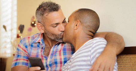 Happy Gay Couple Holding Mobile Phone And Kissing
