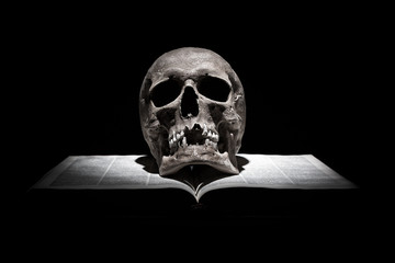 Human skull on old open book on black background under beam of light