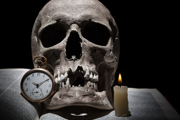 Human skull on old open book with burning candle and vintage clock on black background under beam of light close up