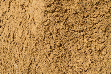 Texture of the sand. Background Industrial sand for construction works. Natural material for bricks and concrete products - loose rock, which grains of feldspar, mica, quartz and other minerals.
