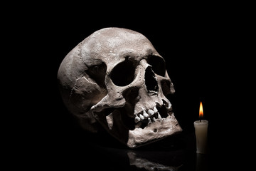 Human skull with burning candle on black background with reflection close up