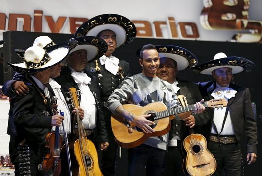Mercedes Formula One driver Lewis Hamilton of Britain plays a guitar next to a mariachi band at the Coliseo Arena during a promotional event in Mexico City