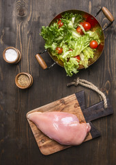 Fresh salad with cherry tomatoes, spices and herbs, in a copper pot, with raw chicken breast on a cutting board, sports dinner on wooden rustic background top view