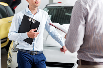 Serious salesman telling with buyer in car dealership