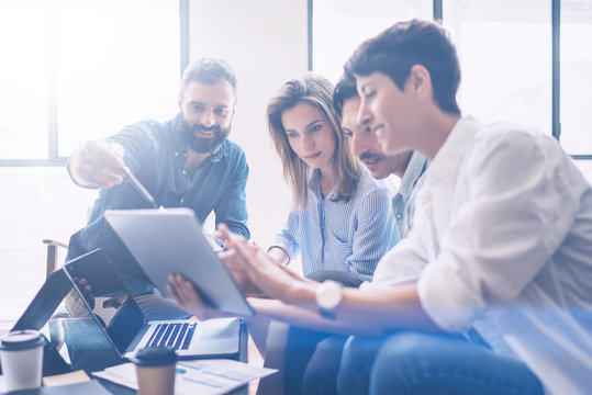 Business meeting concept.Coworkers team working new startup project at modern office.Analyze business documents, using touch tablet.Blurred background.Horizontal