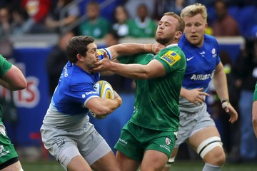 Saracens' Alex Goode battles with London Irish' Tom Cruse in the first half during the first ever English Premiership rugby match played in the United States in Harrison
