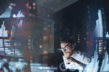 Concept of digital diagram,graph interfaces,virtual screen,connections icon.Young finance analist working at modern office.Man using contemporary laptop at night,blurred background.Horizontal. Wall mural