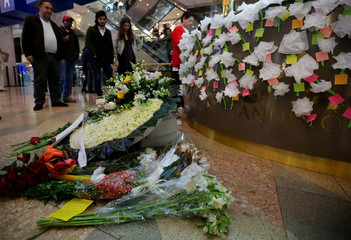 People leave flowers at the Andino shopping center after an explosive device detonated in a restroom on Saturday, in Bogota