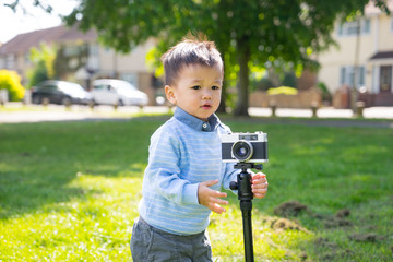 asian baby use a vintage camera
