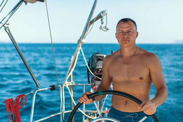 Young man with naked body at the helm of a sailing yacht boat.