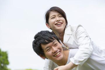 幸せカップル 屋外で彼女を背中におんぶする瞬間イメージ