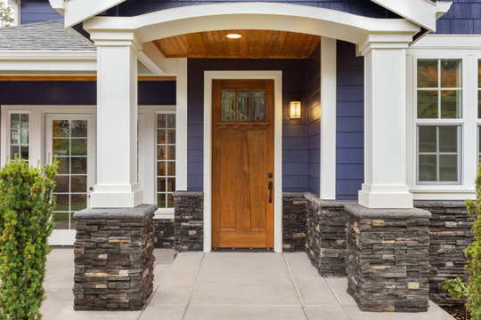 New Luxury Home Exterior Detail: New House Front Door and Covered Patio with Arch, Columns, and Elegant Design