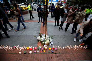 People stand next to candles lit for victims after an explosive device detonated in a restroom at the Andino shopping center on Saturday, in Bogota