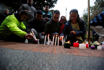 People light candles as a tribute to victims after an explosive device detonated in a restroom at the Andino shopping center on Saturday, in Bogota