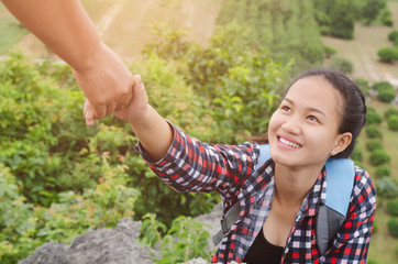 hand hold helping young woman traveler on top mountain