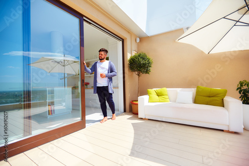 handsome man enjoys life on rooftop terrace with open space kitchen and sliding doors & handsome man enjoys life on rooftop terrace with open space kitchen ...