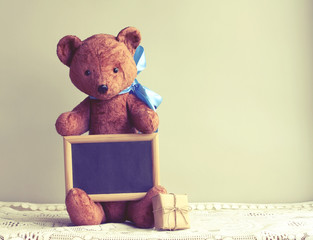 Old worn toy bear with blue bow, photo frame, gift box