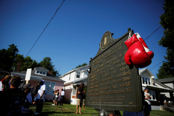 Boxing gloves are seen hanging on a historical marker outside Muhammad Ali's childhood home as mourners gather for the funeral procession for the three-time heavyweight boxing champion in Louisville, Kentucky, U.S.