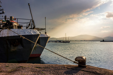 Boats docked to a mooring bollard in the  port of Sozopol at sunset