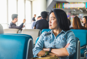 asian Woman waiting for flight at airport terminal for departure Abroad,travel concept